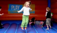 Little girl in green trousers and pale top. Arms held out she's mid bounce on a bouncy castle