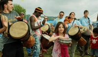 Girl in a pink t-shirt joining in with a group of drummers at the Wychwood festival