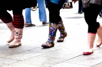 Close-up of brightly coloured wellies on the feet of 3 girls walking down the street