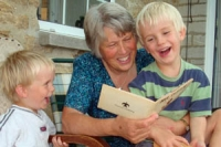 An older woman with grey hair reads to her two grandsons