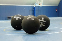 three black kinballs in a sports hall