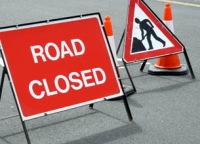 road works and road closure signs and orange and white cones