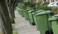 residential street lined with green wheelie bins
