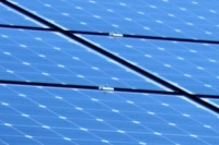 close-up of a number of solar panels, blue with reflected sky