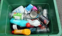A green recycling box full of recyclables