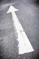 White painted arrow on a road point ahead