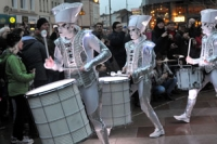 Performance artists dressed in white costumes and hats, with white painted faces, playing drums in front of an animated crowd