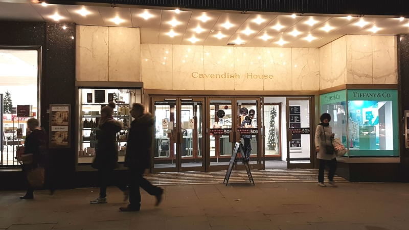 Shoppers at night walking in front of House of Fraser at Cavendish House