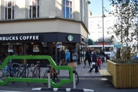 busy high street scene with bike racks, planters, coffee shop and bus in the background