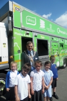 Children in school uniform stand with the mayor in suit and mayoral chain in front of a green recycling vehicle, smiling and squinting into the sun