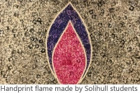 artwork made with hand prints. A red and purple flame against a yellow/grey background. Captions says 'handprint flame made by Solihull students'