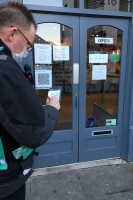 One of our community protection officers standing outside a shop, wearing a mask and green high viz bib, writing in a small notebook