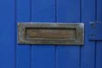 Closeup of an iron letterbox in a blue painted wooden door