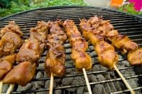 skewers of meat cooking on a barbecue